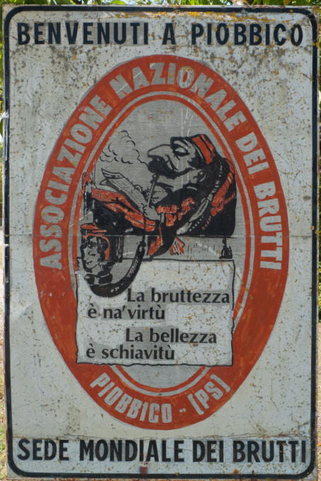 Piobbico: sign that reads 'Benvenuti a Piobbico - sede mondiale dei brutti' (Welcome to Piobbico world headquarters of the ugly)