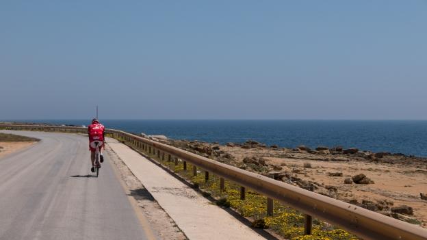 Cyclist on the coast road near Mazara del Vallo