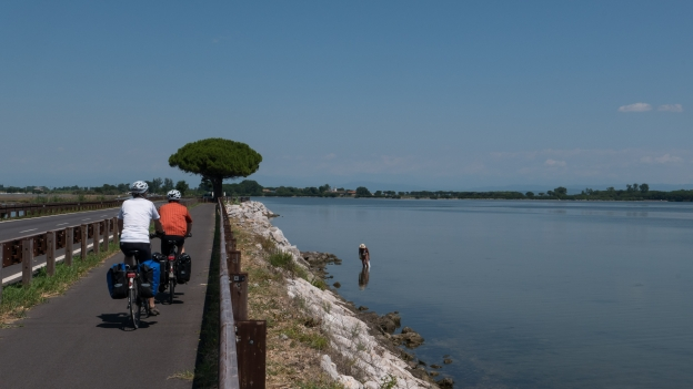 Cyclists on the Ciclovia Alpe-Adria Radweg (FVG1) cycleway on the causeway to Grado