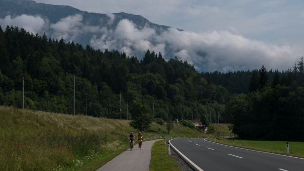 Cyclists on the Ciclovia Alpe-Adria Radweg approaching the border with Italy
