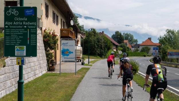 Cyclists on the Ciclovia Alpe-Adria Radweg near the Italy-Austria border