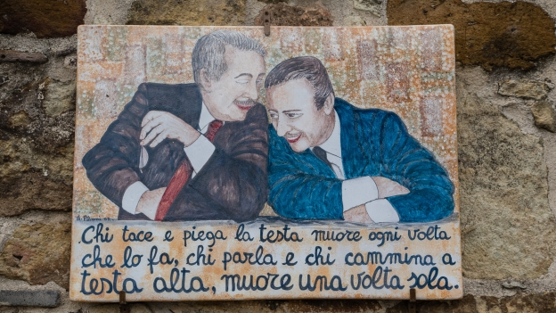 Mural of Paolo Borsellino and Giovanni Falcone. Translation of the text: 'those who keep quiet, and bow their heads, die every time that they do it: whoever talks and walks with their head held high dies only once'.
