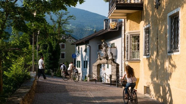 Cyclists and pedestrians on the Brennerradroute on the riverside in Brixen (Bressanone)