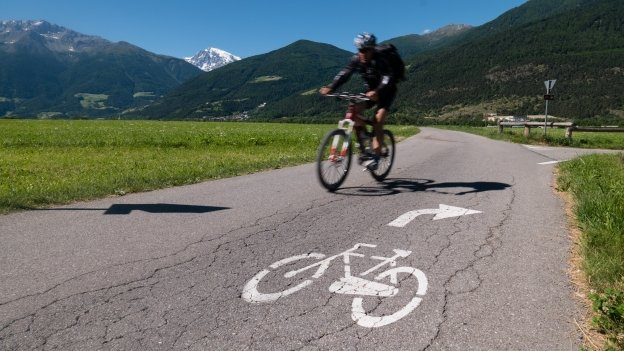Cyclist on a  cycleway near Schlanders (Silandro) with the Ortler in the distance