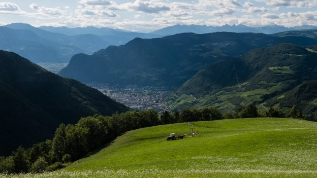 A farmer cuts hay in the meadows high above Bozen (Bolzano) and the Etsch (Adige) valley