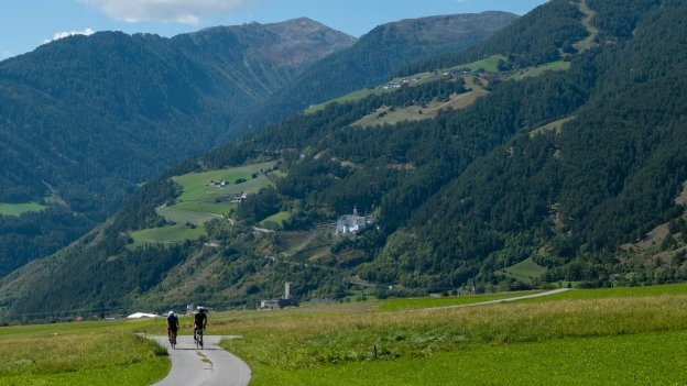 Cyclists riding a cycle route near Burgeis with the Stift Marienberg (Marienberg Abbey) in the distance