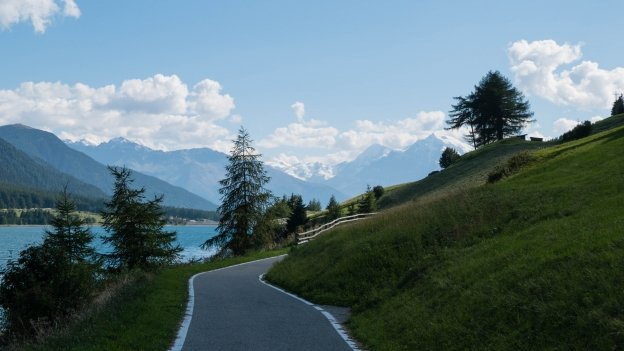 The Etschradroute cycleway on the western shore of the Reschensee (Lago di Resia), looking south towards the snow-covered Italian Alps